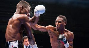 "PHOTO CREDIT: DENZEL BROWN / KNArlydesignz.net Robert Easter Jr.,  AKA ""Trouble"", lands a punch on his opponent, Richard Commey."