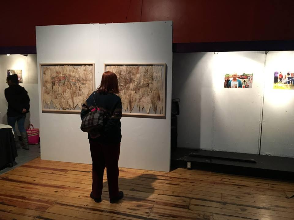 An attendee of a reception for the opening of the Rasquache Art Residency exhibition at Sofia Quintero Art and Cultural Center looks at the artwork on display.