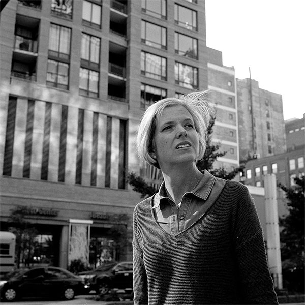 """""""She doesn't know I took that photo— and those are always the best ones,"""" says Dickerson. """"I was in Chicago and it was windy. I was at this corner and I saw this woman.. she kept looking back and forth. You could tell something was on her mind. She had her back turned, but something told me she was going to turn around again. The moment she did, the wind happened to blow and I took that shot. It captured her mood. She was really looking for someone and couldn't find them."""""""
