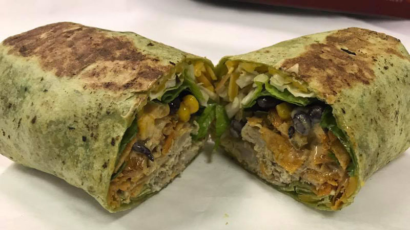 Chicken Fiesta Wrap ($8), stuffed with chicken (or pork), cabbage, chopped greens, cheddar, jalapenos, tortilla strips, black beans, and corn.