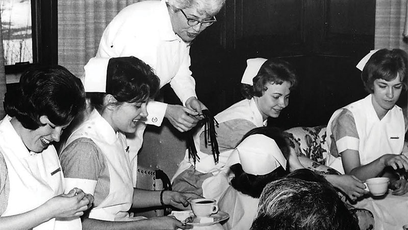 The placement of the black band on the school cap followed a tradition. Here student nurses are guided by school director, Miss Klinger, in the applying and securing the band.  (Photo courtesy of The White Cap yearbook of the Toledo Hospital School of Nursing, 1965)
