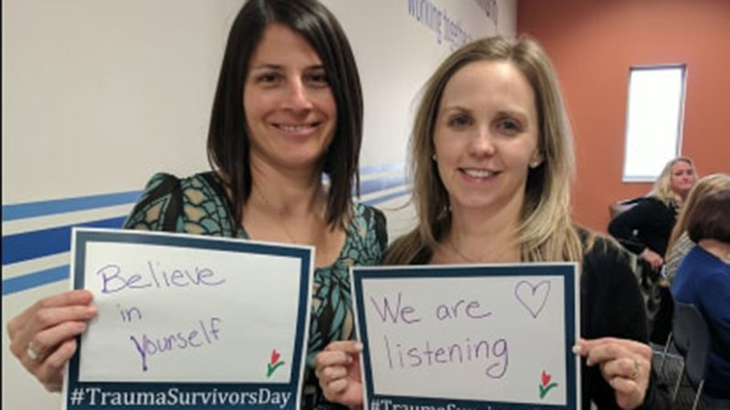 Dr. Adrienne Fricker-Elhai and Alicia Komives holding messages to survivors.