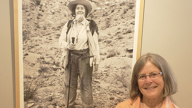 Dr. Catherine Badgley from University of Michigan poses next to her bearded portrait.