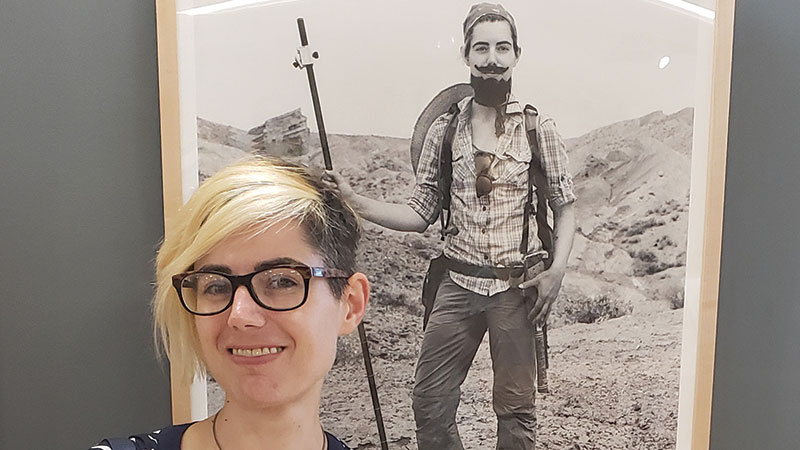 Dr. Katharine Loughney from University of Michigan poses next to her bearded portrait.