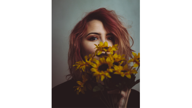 """""""This is a photo I took for a local musician, Emma Lee. Her personality and aesthetic really scream sunflowers and I really like the way I was able to play off the yellow of the flowers and the pink of her hair. I also love how part of her face is covered as if hiding something, but you can just make out her smile coming through the blooms. Emma is hands down one of my favorite subjects to shoot and I am lucky as an artist to work with people like her."""""""