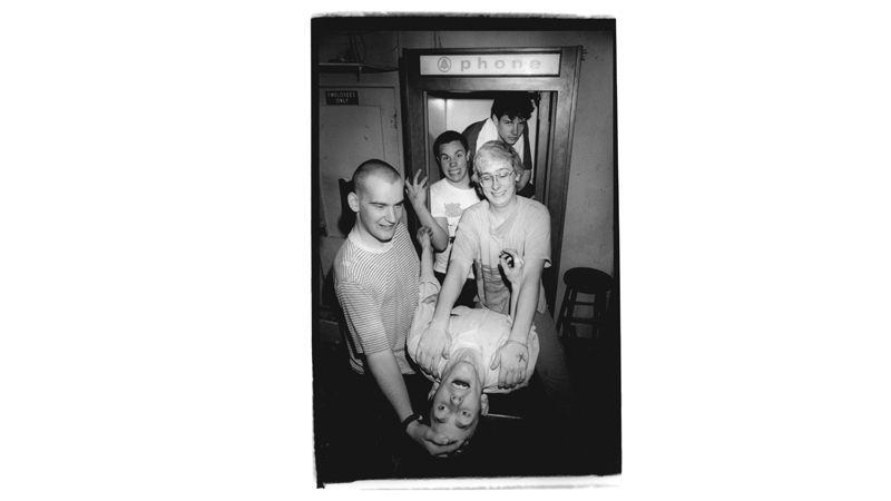Minor Threat in phone booth, Austin, Texas, 1983. Foreground: Jeff Nelson. L to R: Ian MacKaye, Steve Hansgen, Brian Baker, Lyle Preslar. Photo Credit: Bill Daniels.