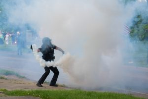 An officer throws a tear gas canister toward protestors on the opposite sidewalk on Franklin Avenue. (Photo credit: Christy Frank)