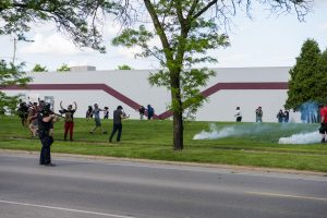 A police officer fires on protestors along Franklin Avenue. People began retreating further back into the grass. (Photo credit: Christy Frank)