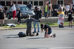 Don Schiewer, kneeling left, and Lee Johnson, kneeling right, attempt to protect the protestors further ahead from police. (Photo credit: Christy Frank)