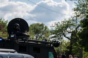 A police officer's gun smokes from the top of his armored vehicle after firing at protestors along Bancroft Street. (Photo credit: Christy Frank)