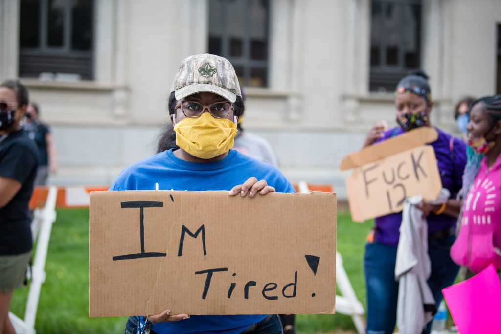 Woman holding a poster saying I'm Tired