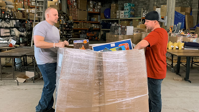 Chris Clay (left) and Chuck Popovich begin unboxing a pallet for their resale business on A&E's Extreme Unboxing. Credit goes to A&E2020.